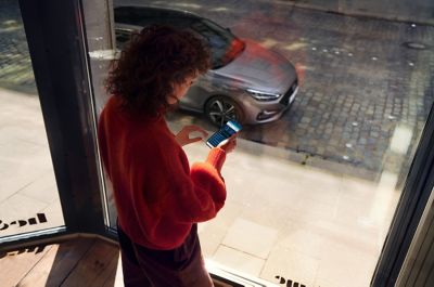 Woman standing by the window, looking at the Bluelink app on her phone. Her Hyundai i30 Fastback is parked on the street.